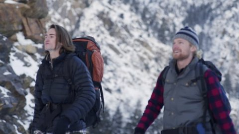 Excited Friends Walk Past Camera On Backpacking Adventure In Snowy Utah Mountains