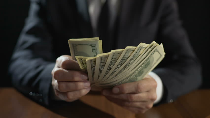 Corrupt official counting bundle of money, taking bribe for abuse of power