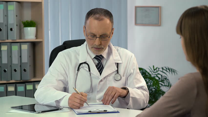 Family doctor talking to patient and filling out medical insurance, health care | Shutterstock HD Video #24018658