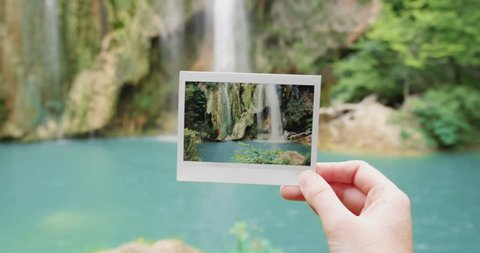 Close up hand holding polaroid photograph in front of waterfall travel concept