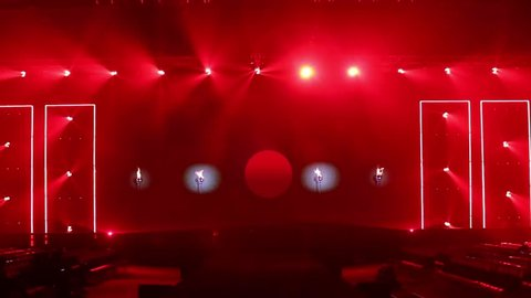 Fashion Show Catwalk Runway Stage in Reddish atmosphere with smoke, spotlight par lighting in red color over hanging construction with black walk way with empty seat, copy space