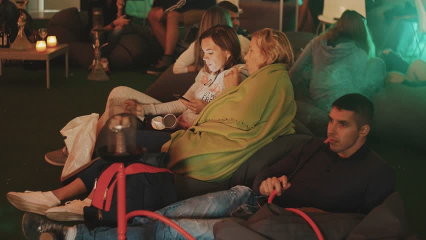 SAINT PETERSBURG, RUSSIA - AUGUST 28, 2016: Young people smokes hookah talking and eating chips sitting on bean bags inside of a tent during festival. Changing colorful lights | Shutterstock HD Video #24049678