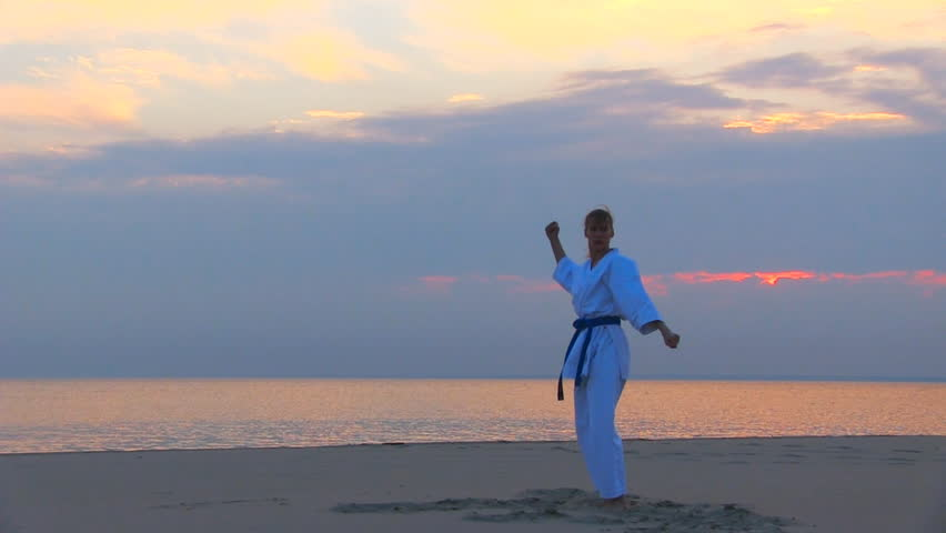 young woman training karate on sunset beach