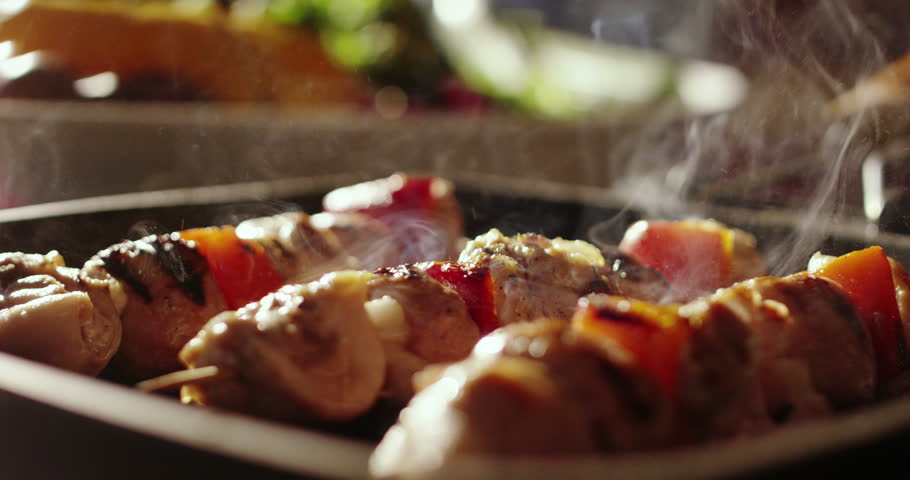 cinemagraph of skewers of meat with vegetables cooked on a spit in a pan #24088150