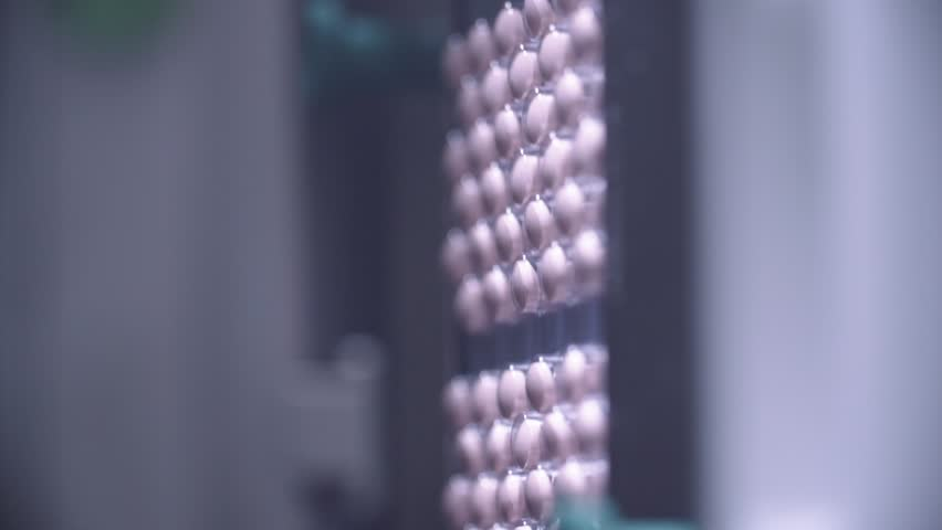 Automated packing at drug production. Closeup slow motion shot of an automated pill packaging machine.Tablets in Packages on a Conveyor. Pharmaceutical machinery for medicine production Pills.