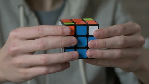Boys hands solving rubik cube and showing thumb.