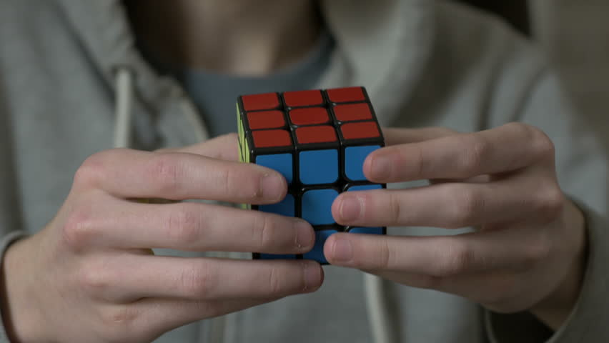 Boys hands solving rubik cube and showing thumb.   Shutterstock HD Video #24126661