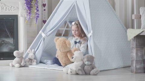A child plays with toys, talking with them and embraces a soft toy. Little girl in teepee tent. Playroom for kids with Teepee or DIY tent. Wigwam for children in a room.
