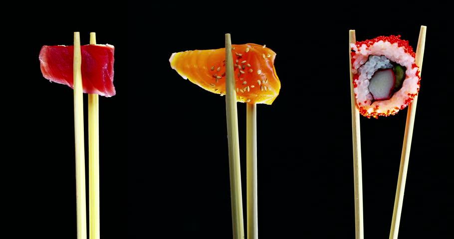 composition of sushi,sashimi,uramaki and nighiri.typical Japanese dish consisting of rice, salmon, tuna,shrimp and fish eggs on a black background.Concept:Japanese restaurant,sushi,oriental tradition