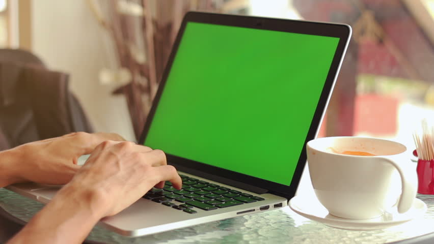 Close-up of male hands using laptop with green screen at cafe, man's hands typing on laptop keyboard in interior, side view of freelancer using computer in cafe | Shutterstock HD Video #24134812