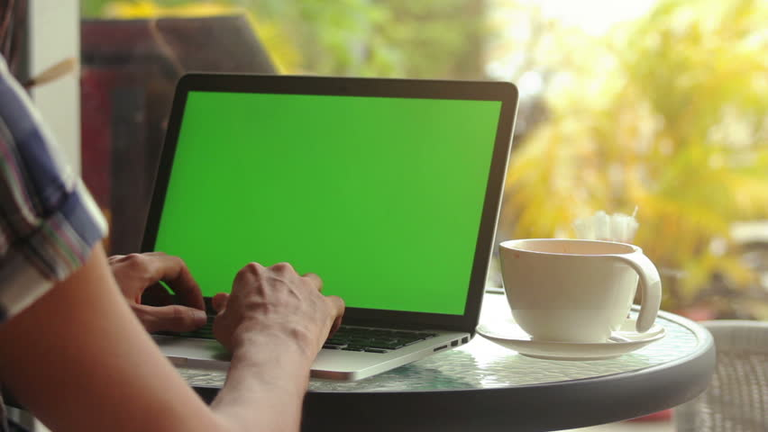Close-up of male hands using laptop with green screen at cafe, man's hands typing on laptop keyboard in interior, side view of freelancer using computer in cafe | Shutterstock HD Video #24134818