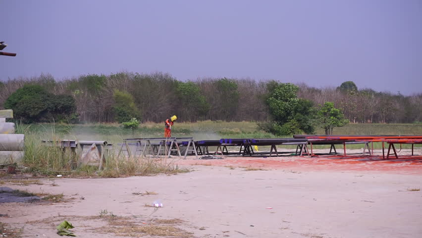 Landscape worker are sandblasting pipeline. For prepare the surface before painting