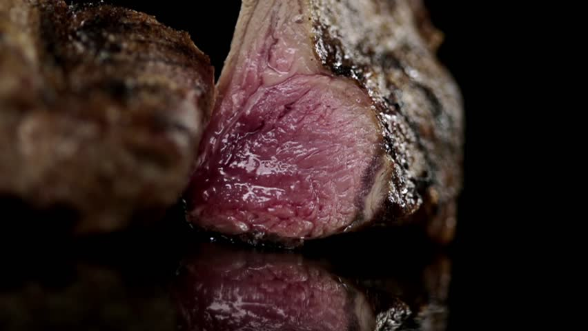 CLOSE UP FOOD: rack of lamb is cut in half slow motion
