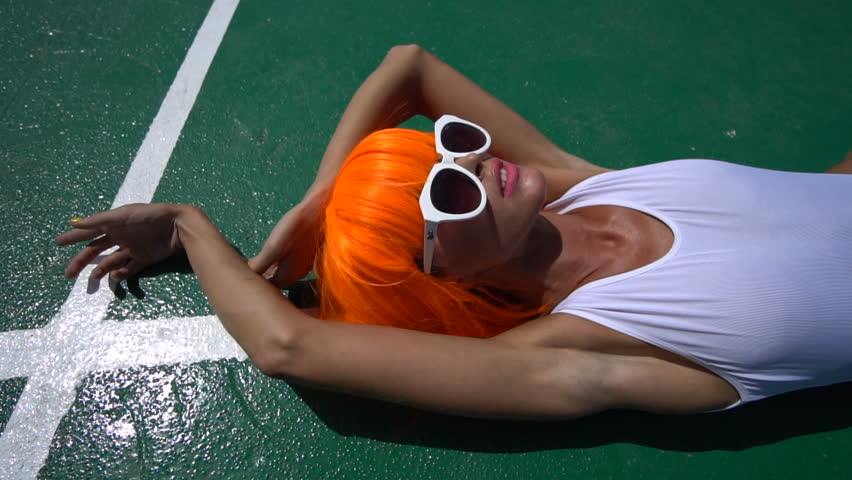 Closeup face of sexy woman in modern futuristic style lying on her back isolated on green play field. Creative look of woman wearing white swimsuit, sunglasses and orange wig in hot summer day