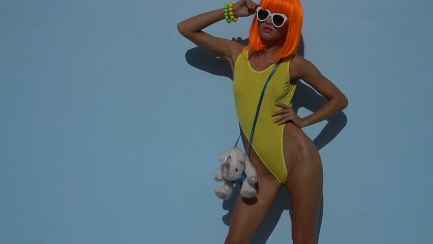 Sexy beautiful woman in modern futuristic style posing during sunny summer day over blue wall background. Creative look of woman in yellow swimsuit, orange wig and white sunglasses - slow motion video