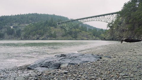 From the shore of Whidbey Island, looking North towards Fidalgo Island. Waves break over pebbles in foreground. Looking up at Deception Pass Bridge; traffic moves over two steel cantilever bridges.