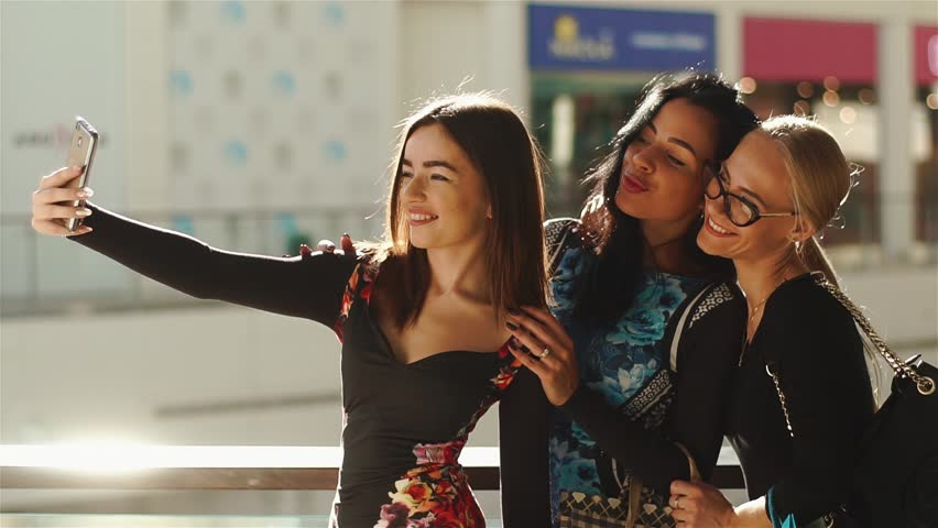 Charmed women taking selfie after shopping. Girls smiling. They posing for photos, taking their hands on hair, face and glasses. Have many colorful shopping bags.   Shutterstock HD Video #24185566