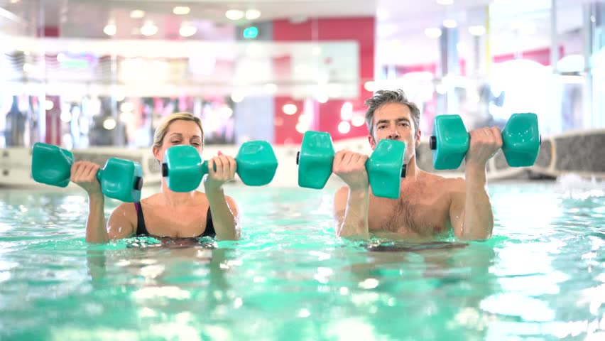 Group Of Smiling Women With Aqua Tubes Doing Exercise In