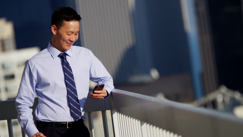 Male Asian Chinese business manager working hot spot on rooftop using mobile technology RED DRAGON