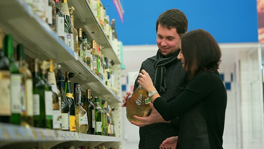 The girl with the to boyfriend choosing white wine for barbecue parties