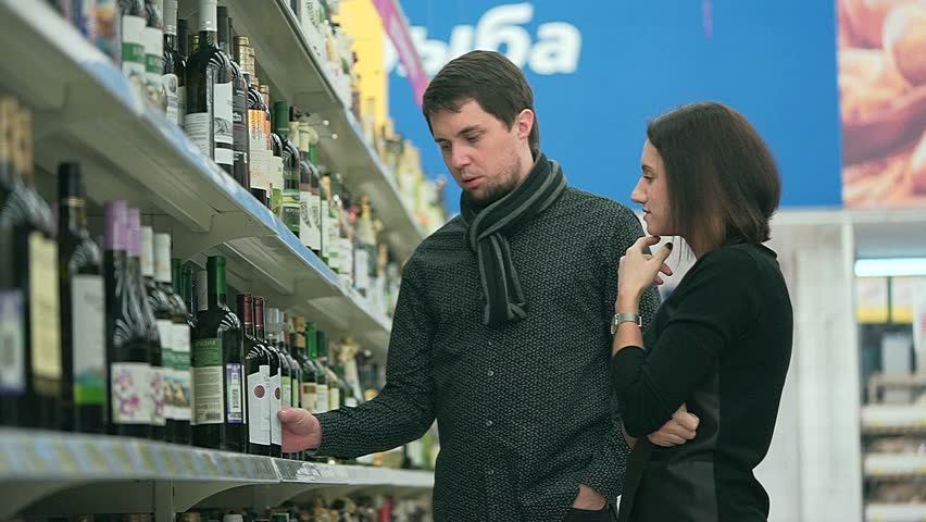 Young woman and her boyfriend chooses a bottle of wine for the bbq party