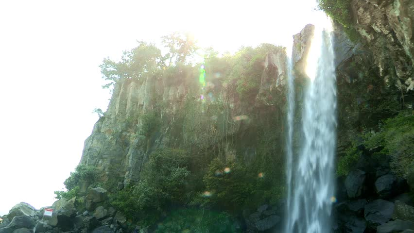 a datyime view of a waterfall in Jeju island