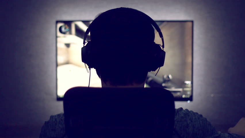 Gamer from back in headphones sits in front of a monitor with video game in dark room | Shutterstock HD Video #24246968