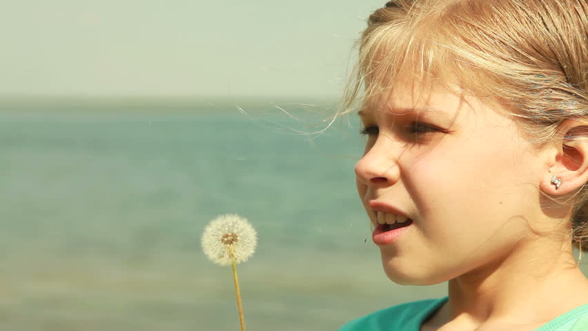 Girl blowing a dandelion off making a wish