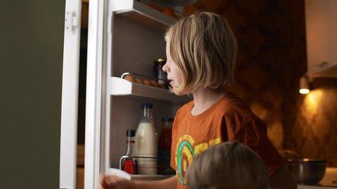 Young blonde kid taking bottle of yogurt from fridge than closing it in slowmotion