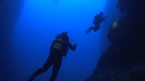 scuba divers exploring a cave underwater cave dive