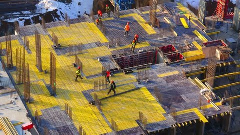 Top view of a group of construction workers at construction site who are laid metal reinforcements for the new floor slabs. Time lapse