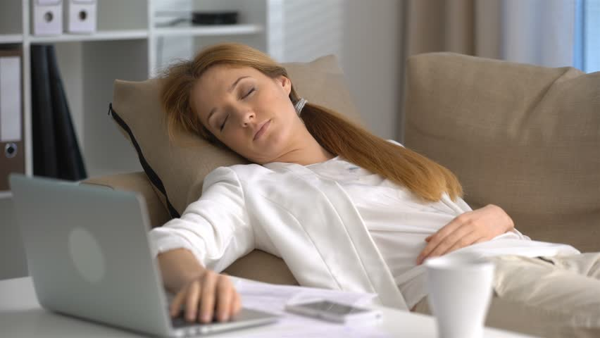 Tired businesswoman sleeping on the couch in the office with laptop and phone. Dolly shot | Shutterstock HD Video #24335348