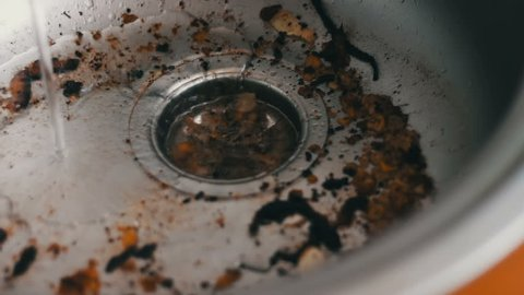 Dirty clogged sink by various food scraps and fat close up view