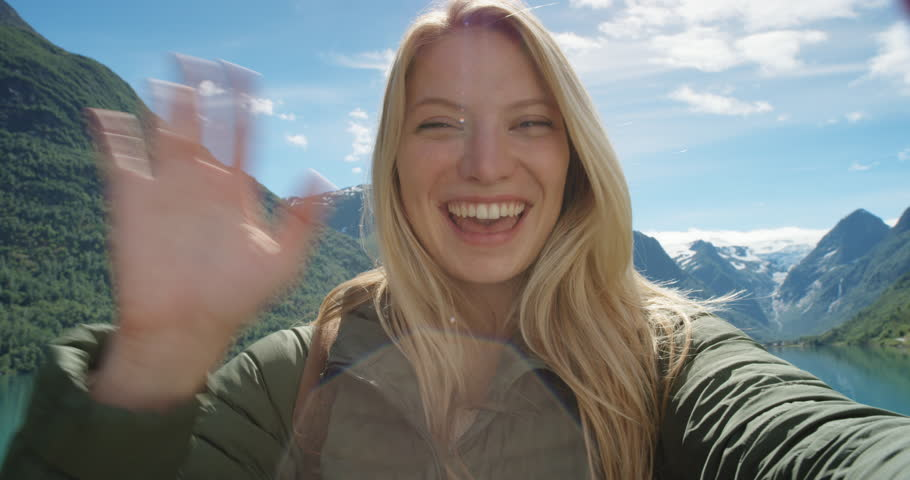 Beautiful woman having video chat using smartphone outdoors sharing travel adventure  friends showing lake and glacier Girl filming selfie video photo for social media  Norway vacation slow motion | Shutterstock HD Video #24370124