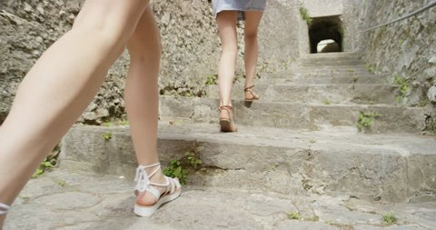 Tourist women exploring old town close crop from behind Girl walking through Italian street Best friends travelling enjoying summer vacation travel adventure in Ravello Amalfi Italy