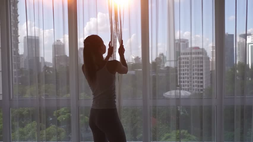 Super slow motion. Young woman uncover the big window and looking out her apartment on the city buildings. Sunrise in the city.