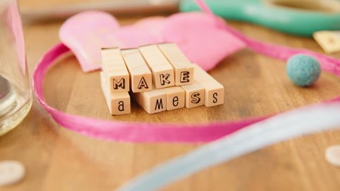 A hand puts the finishing touches on an inspiring message, made out of wooden letter blocks on a wooden craft table, bursting with pretty craft supplies, in an artists' studio. Make a Mess.