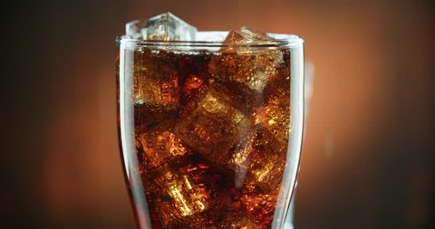 Cola with ice. close-up for a very large glass of cold coke with ice cubes rotation