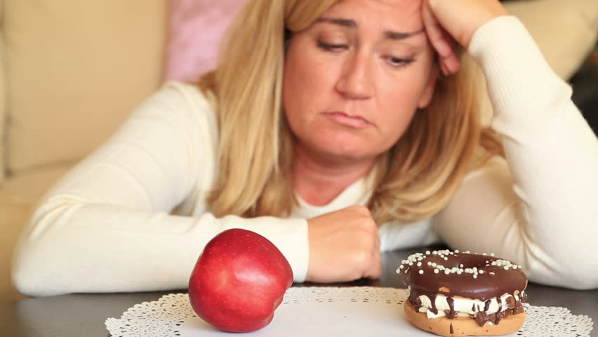 Attractive middle aged woman deciding between a healthy and unhealthy. Diet and choice people concept | Shutterstock HD Video #24431858