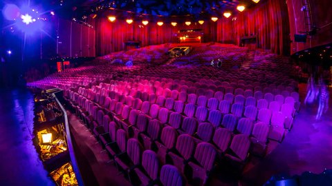 Spectators gather in the auditorium and watch the show in theatre timelapse. Large hall with red armchairs seats. Viewers filling places until turn off the light. View from right side