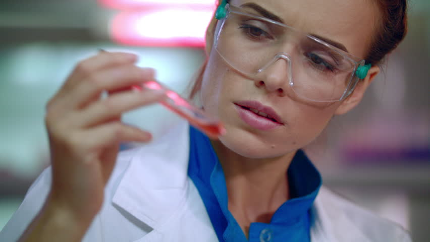 Female doctor analyzing liquid in test tube. Closeup of lab doctor doing medical research. Medical researcher doing clinical trials. Woman scientist doing medical research