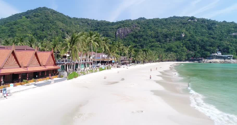 Flying along the beautiful Haad Rin Beach on Koh Phangan, Thailand. Tourists enjoying this white sand beach which is famous for its Full Moon Party once a month.