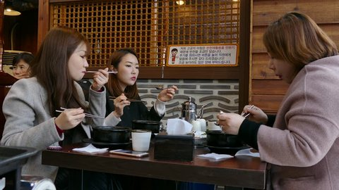 SEOUL, SOUTH KOREA - DECEMBER 2016 - Traditional restaurant in Seoul, South Korea, Asia. Asian people, tourists, female clients, customers, workers eating Korean food during lunch break