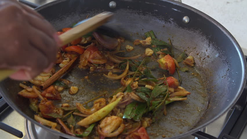 Close up shot of a Sri Lankan chef stirring spices and vegetables for a sizzling sri lankan chicken curry in a frying pan.