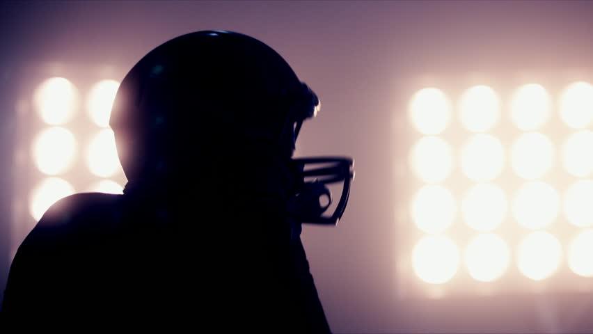CU Silhouette of male American football player putting on his protective helmet against bright stadium illumination lights. Bearded man. 50 FPS 4K UHD RAW edited footage