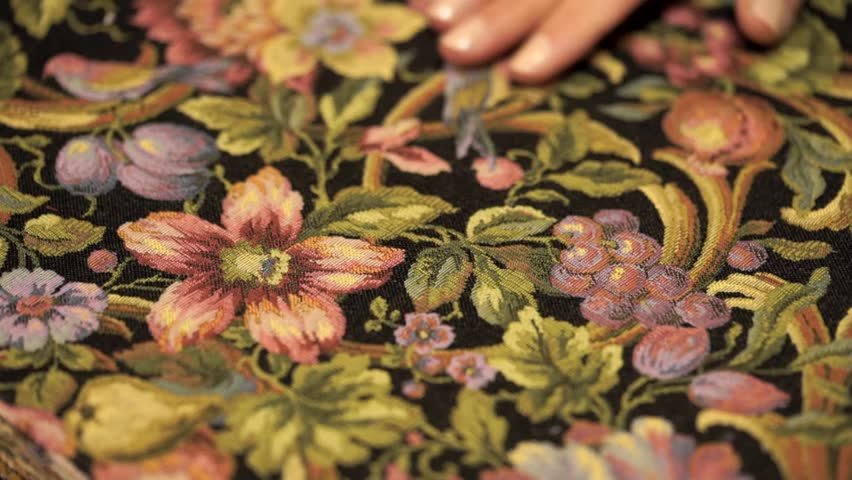 girl looks through a tapestry samples. sided lint-free cloth with ornamental composition
