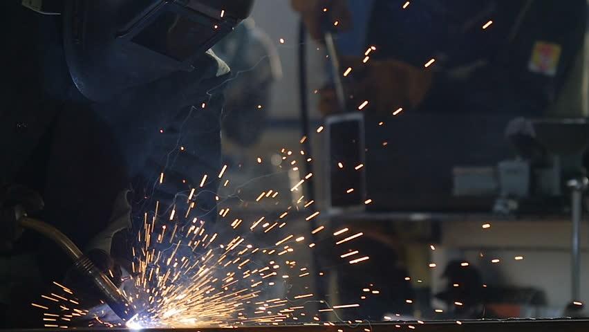welder in equipment works with welding machine inside production workshop bright sparks fly around in darkness