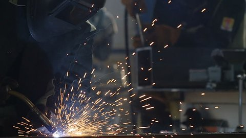 welder in equipment works with welding machine inside production workshop bright sparks fly around in darkness