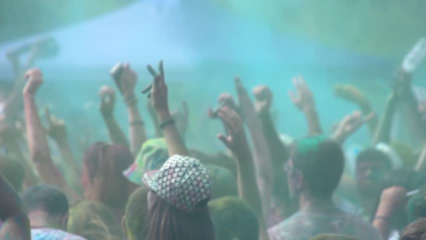 Youth crowd in a colorful summer disco concert. People crowd in colorful holi concert