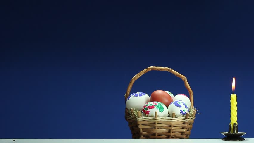 The easter basket with hand painted eggs turns and around it the on a blue background revolves wicker basket with hand painted easter eggs hd stock negle Gallery